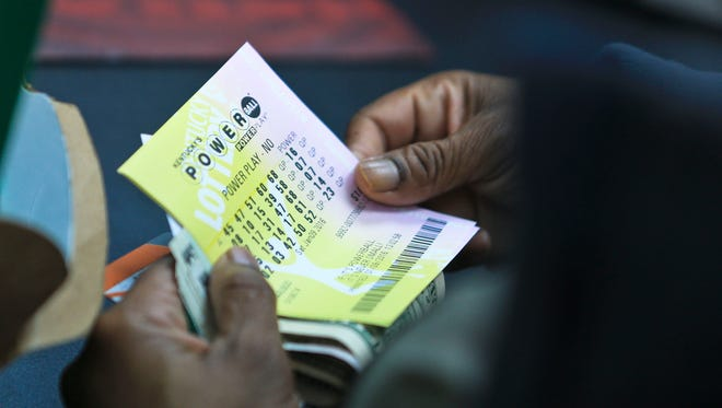 Debra Jones inspects her Powerball tickets after purchasing them at Bader's Food Mart in downtown Lousville Saturday.