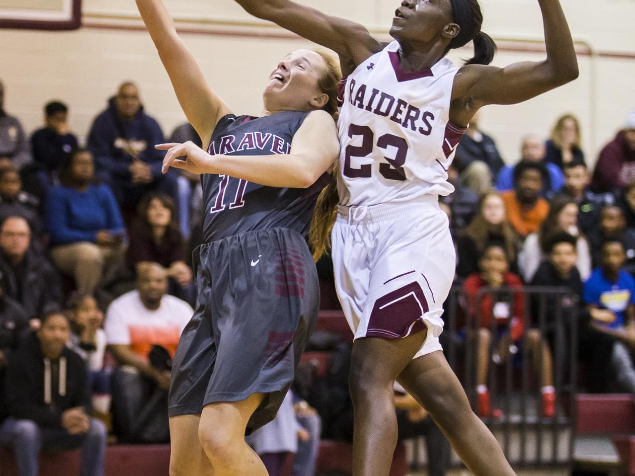 Caravel's Katherine Spae (No. 11) is fouled by Concord's Zhan'e Snow (No. 23) as she puts up a shot in the first half of Caravel's 42-26 win over Concord at Concord High School on Monday night.