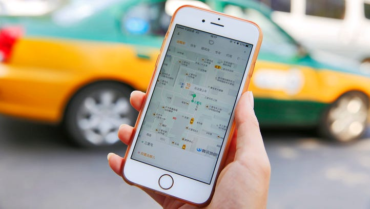 A commuter shows the Didi Chuxing app on her iPhone