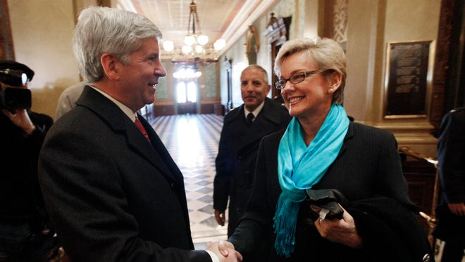 In this file photo from Jan. 1, 2011, Michigan Gov.-elect Rick Snyder, left, shakes hands with outgoing Gov. Jennifer Granholm before inauguration ceremonies in  downtown Lansing.