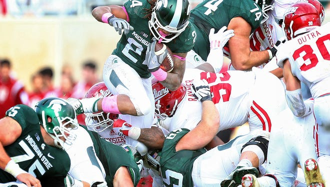 Michigan State running back Gerald Holmes jumps over the pile against the Indiana Hoosiers during the 1st half of a game at Spartan Stadium.
