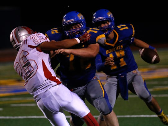 Bloomfield's Tim Moore blocks for quarterback Brendon Charley on Friday at Bobcat Stadium in Bloomfield.