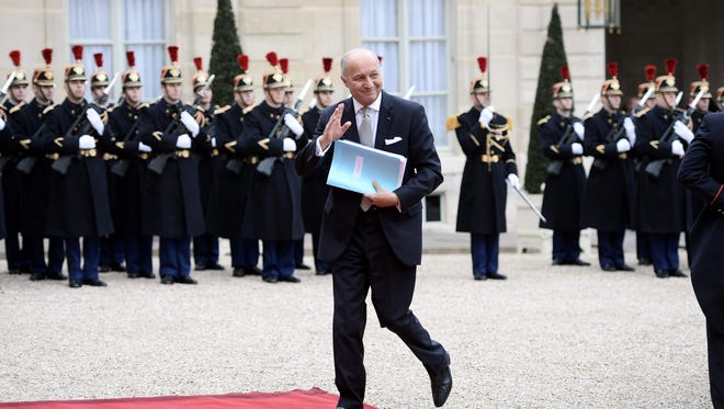 French Foreign Affairs Minister Laurent Fabius waves as he arrives before a meeting with the Iranian president with Iran's President Hassan Rouhani at the Elysee Palace in Paris on Jan. 28, 2016.