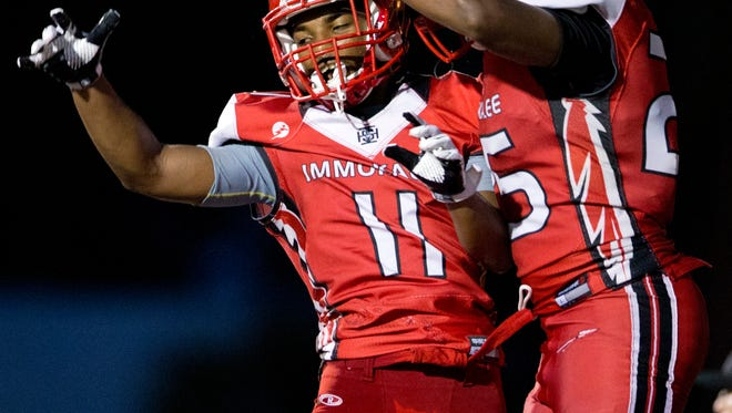 Immokalee's Malcom Jackson (11) and Jevon Thomas (25) celebrate after Thomas scores a touchdown in the first half of action against Barron Collier Friday, September 9, 2016 in Immokalee. At the end of the first half Barron Collier led 21-14.