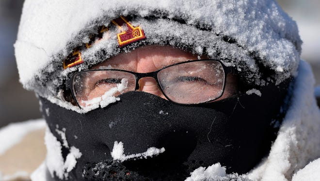Milissa Preiss peers out from behind snow-covered glasses while clearing her Sartell, Minn., driveway on March 3.