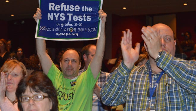 A Brewster parent held up a sign at Purchase College on March 12, urging others to opt out of New York's standardized tests for grades 3 to 8.