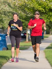 Shannon Fischer, left, and her husband Jason Fischer go for a run in their neighborhood in Ann Arbor.