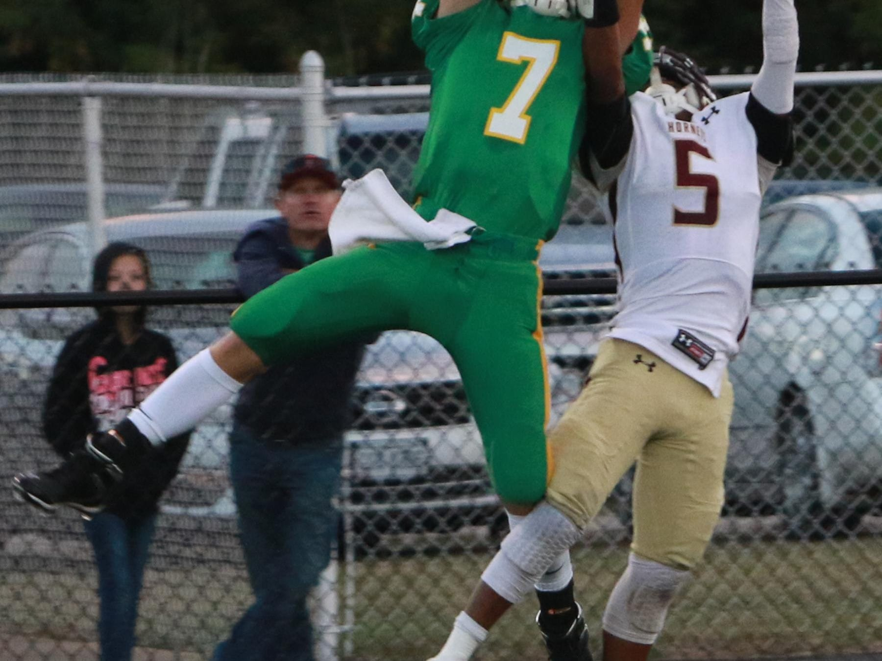 Newark Catholic junior Tanner Lake makes a leaping catch above Licking Heights' Keshawn Moore this past Saturday during the Hornets' 21-13 victory against the Green Wave.