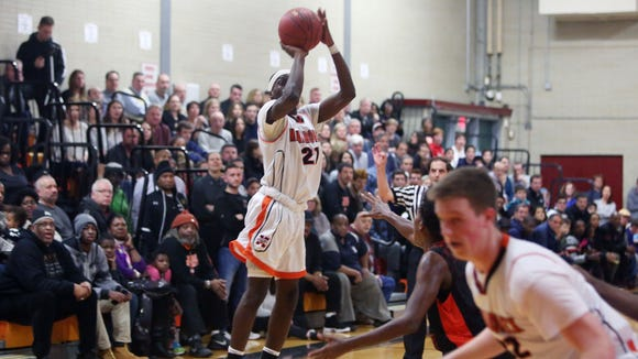 From left, Mamaroneck's Bothanamie Martin (21) puts up a shot against Spring Valley during Section 1 boys basketball playoff action at Mamaroneck High School Feb. 23, 2018. Mamaroneck won the game 49-42.