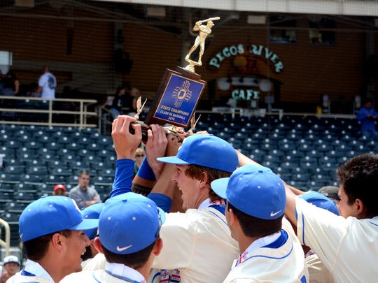 Carlsbad hoists the blue trophy after winning the 2016 6A state championship on May 14 at Isotopes Park in Albuquerque. The Cavemen won their second title in five years, 11th overall.