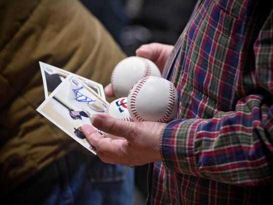 A fan waits in line for autographs from Hector Santiago,