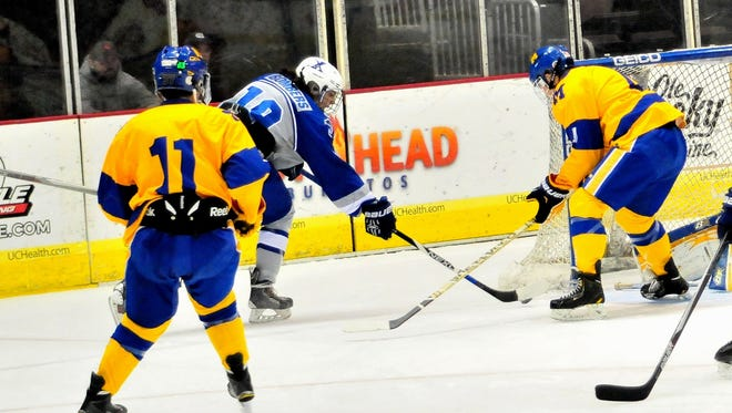 St. Xavier's John Driscoll (19) drops the puck in the backdoor of the goal for the Bombers.