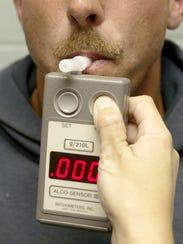 A man blows into a breathalyzer.