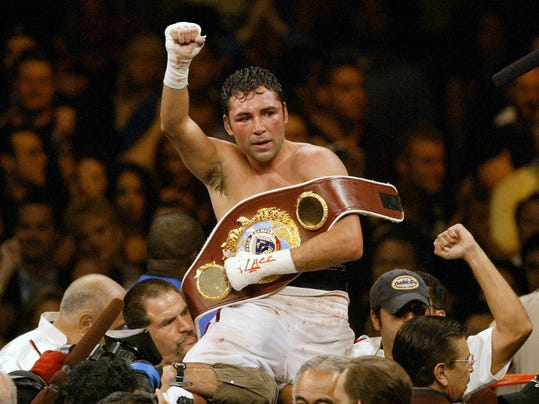FILE - In this June 5, 2004 file photo, Oscar De La Hoya celebrates his unanimous decision victory over Germany's Felix Sturm following their WBO world middleweight title fight in Las Vegas. De La Hoya got drunk the night he won the only boxing gold for the U.S. in the 1992 Olympics, and was still drinking when he lost his last fight to Manny Pacquiao. Now sober after a second stint in rehab he's in a fight of another kind for control of his boxing company. (AP Photo/Joe Cavaretta, File)