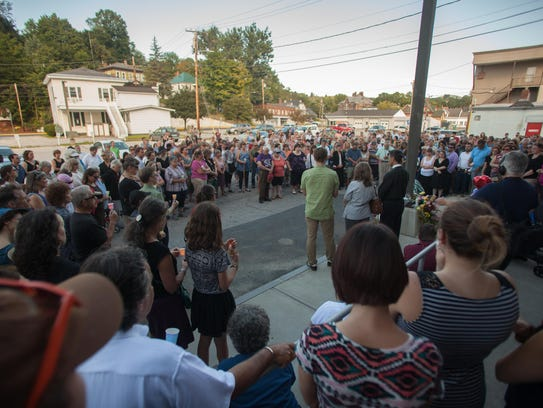 Hundreds gather for a vigil last August behind the