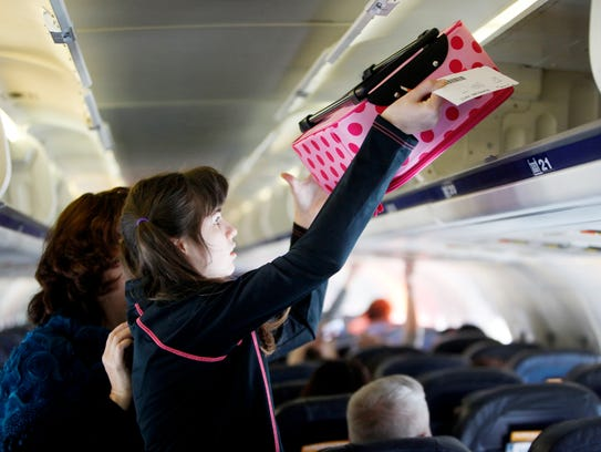 Kelly Arnold, 13, places her carry-on luggage into