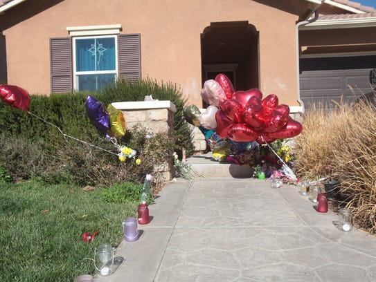 Candles and balloons stand outside of a Perris house