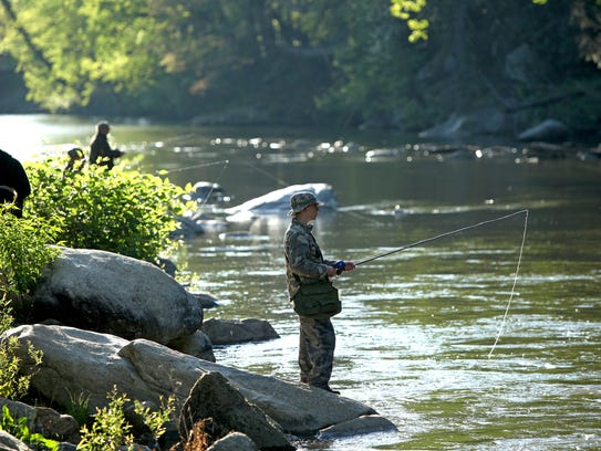 Fishermen line the Rocky Broad River in Bat Cave on