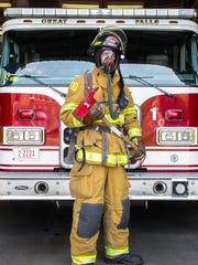 Firefighter Sterling Veltkamp stands in full gear in front of engine No. 1 at Fire Station 1 in Great Falls. Veltkamp is following in his father's footsteps and has been with the department for a year and a half.