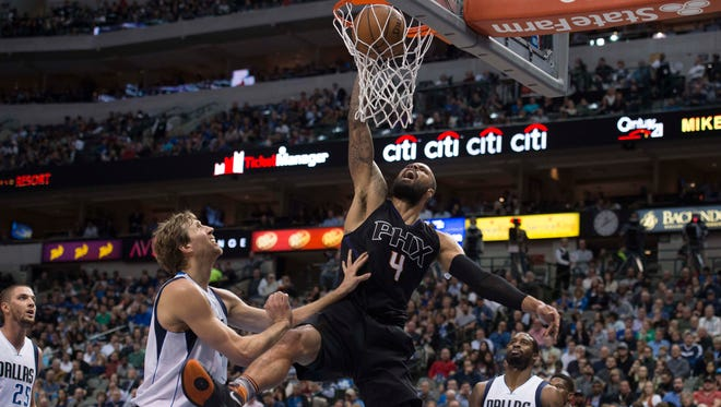 Suns center Tyson Chandler (4) dunks the ball in front of Dallas Mavericks forward Dirk Nowitzki (41) during the first half at the American Airlines Center.