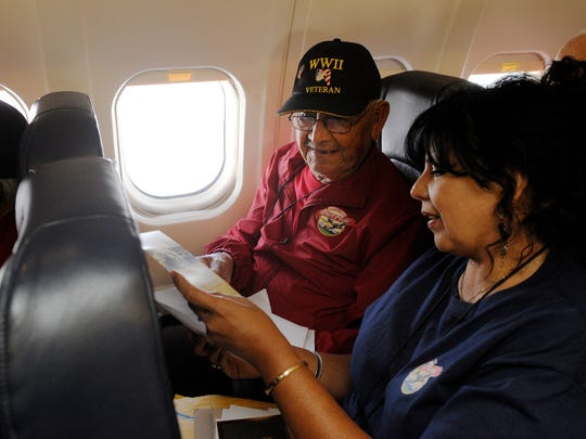 """Manuel Sosa of Dinuba, left, and his daughter, Cindy Jaime, look at cards and letters he received during """"Mail Call"""" during the return flight for the Central Valley Honor Flight. They were returning from a whirlwind 3-day tour of war memorials in Washington, D.C. When he read the letter from her, he cried and hugged her, she said."""