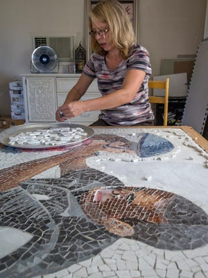 Avondale artist Petra Adams cuts a piece of tile as she works on a mosaic panel honoring Avondale police officers. She is being assisted by high-school students and hopes to complete the mural in October.