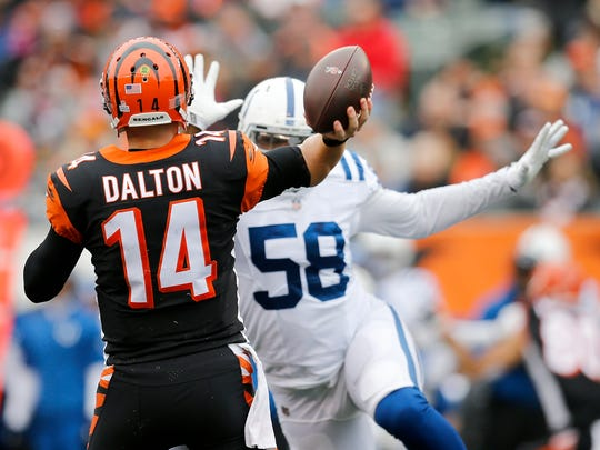 Cincinnati Bengals quarterback Andy Dalton (14) throws with pressure from Indianapolis Colts linebacker Tarell Basham (58) in the second quarter of the NFL Week 8 game between the Cincinnati Bengals and the Indianapolis Colts at Paul Brown Stadium in downtown Cincinnati on Sunday, Oct. 29, 2017.