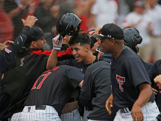 Texas Tech players celebrate with Orlando Garcia, center, after hitting a home run against Delaware during an NCAA college baseball regional game Friday, June 2, 2017, in Lubbock, Texas.