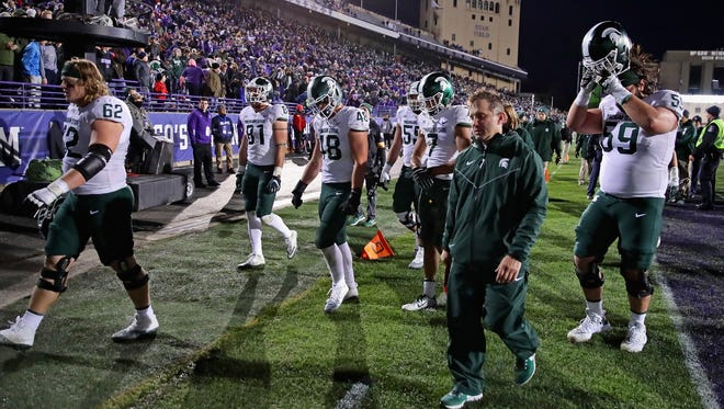 Members of the Michigan State team walk off of the field after MSU's 39-31 triple-overtime loss on Saturday, Oct. 28, 2017, in Evanston, Ill.