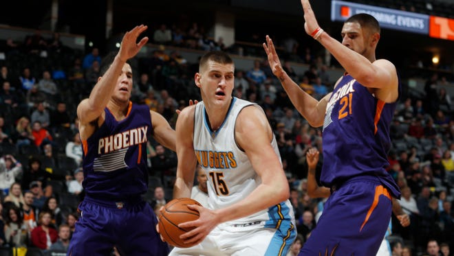 Denver Nuggets forward Nikola Jokic (15) looks to pass the ball as Phoenix Suns guard Devin Booker (1) and center Alex Len (21) defend in the first half of an NBA basketball game Thursday, Jan. 26, 2017, in Denver.