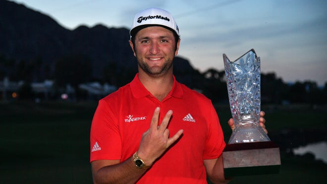 Jan 21, 2018: Jon Rahm gives the forks up gesture for his alma mater Arizona State University while holding the trophy after the final round of the CareerBuilder Challenge golf tournament at PGA West TPC Stadium Course.