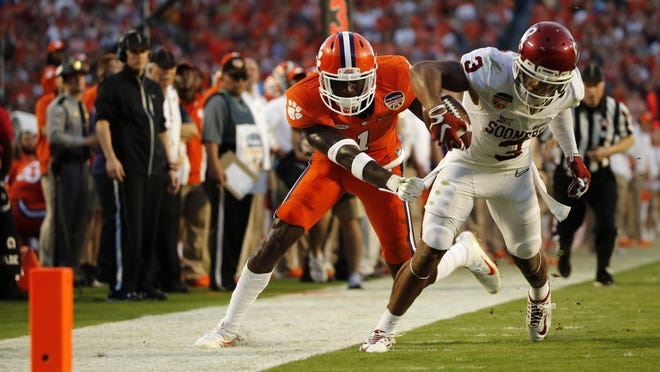 Oklahoma Sooners wide receiver Sterling Shepard (3) tries to pull away from Clemson Tigers and former South Fort Myers safety Jayron Kearse (1) in the second quarter of the 2015 FBS Semifinal at the Orange Bowl at Sun Life Stadium Dec. 31.