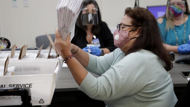 A Miami-Dade County Department of Elections employee gathers vote-by-mail ballots for the Aug. 18 primary election as the canvassing board meets to verify ballot signatures at the Miami-Dade County Elections Department in Doral.
