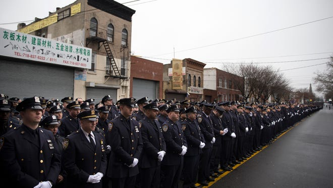Police officers stand at attention during the funeral of New York Police Department officer Wenjian Liu at Aievoli Funeral Home on Sunday in Brooklyn. Liu and his partner, officer Rafael Ramos, were killed Dec. 20 as they sat in their patrol car on a Brooklyn street. The shooter, Ismaaiyl Brinsley, later killed himself.