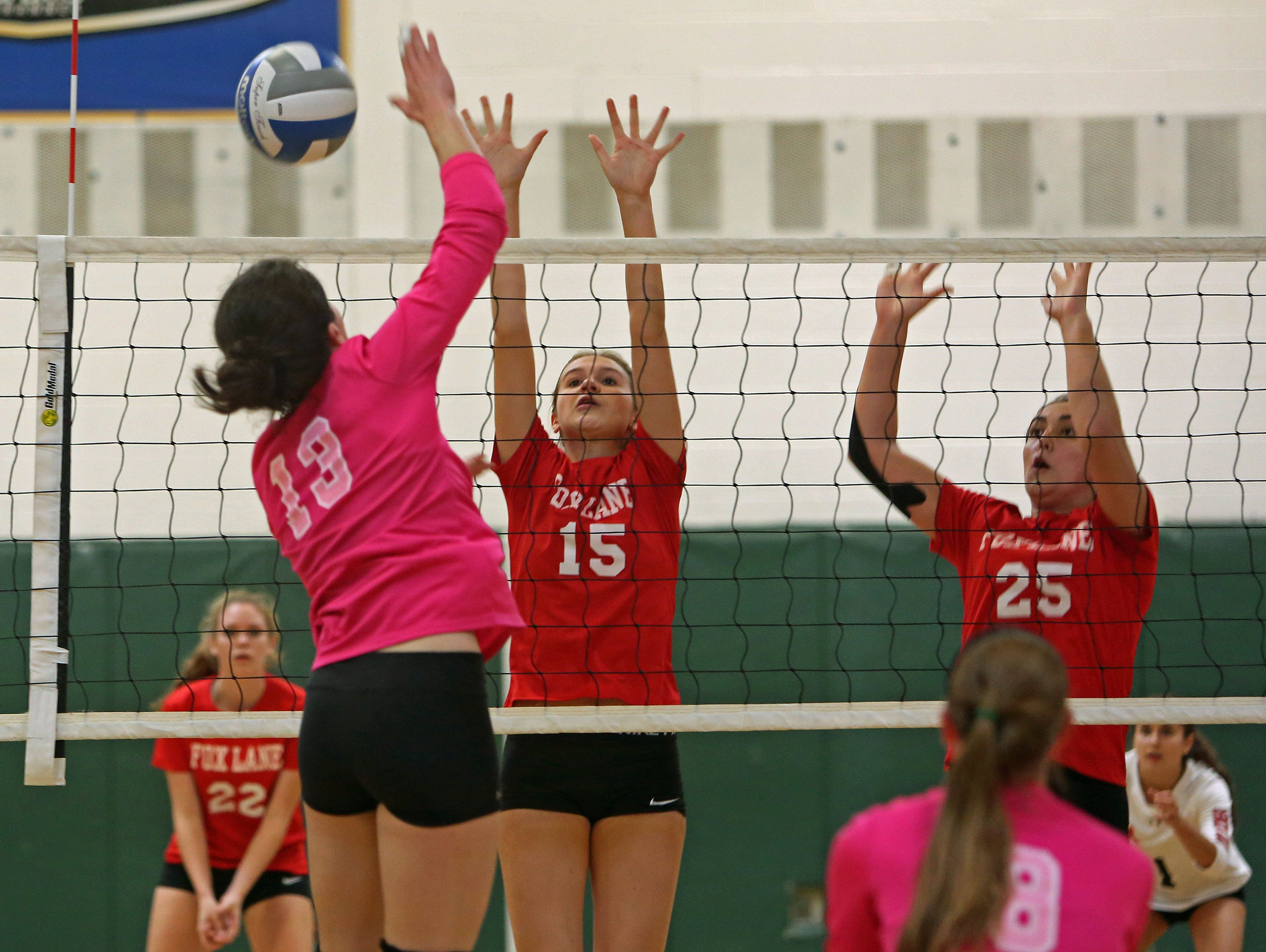 From left, Brewster's Frannie Merkel (13) tries to get a shot by Fox Lane's Kate Alexander (15) and Maria Violante (25) during volleyball action at Brewster High School Oct. 22, 2015. Fox Lane swept Brewster 25-23, 25-23, and 25-16.
