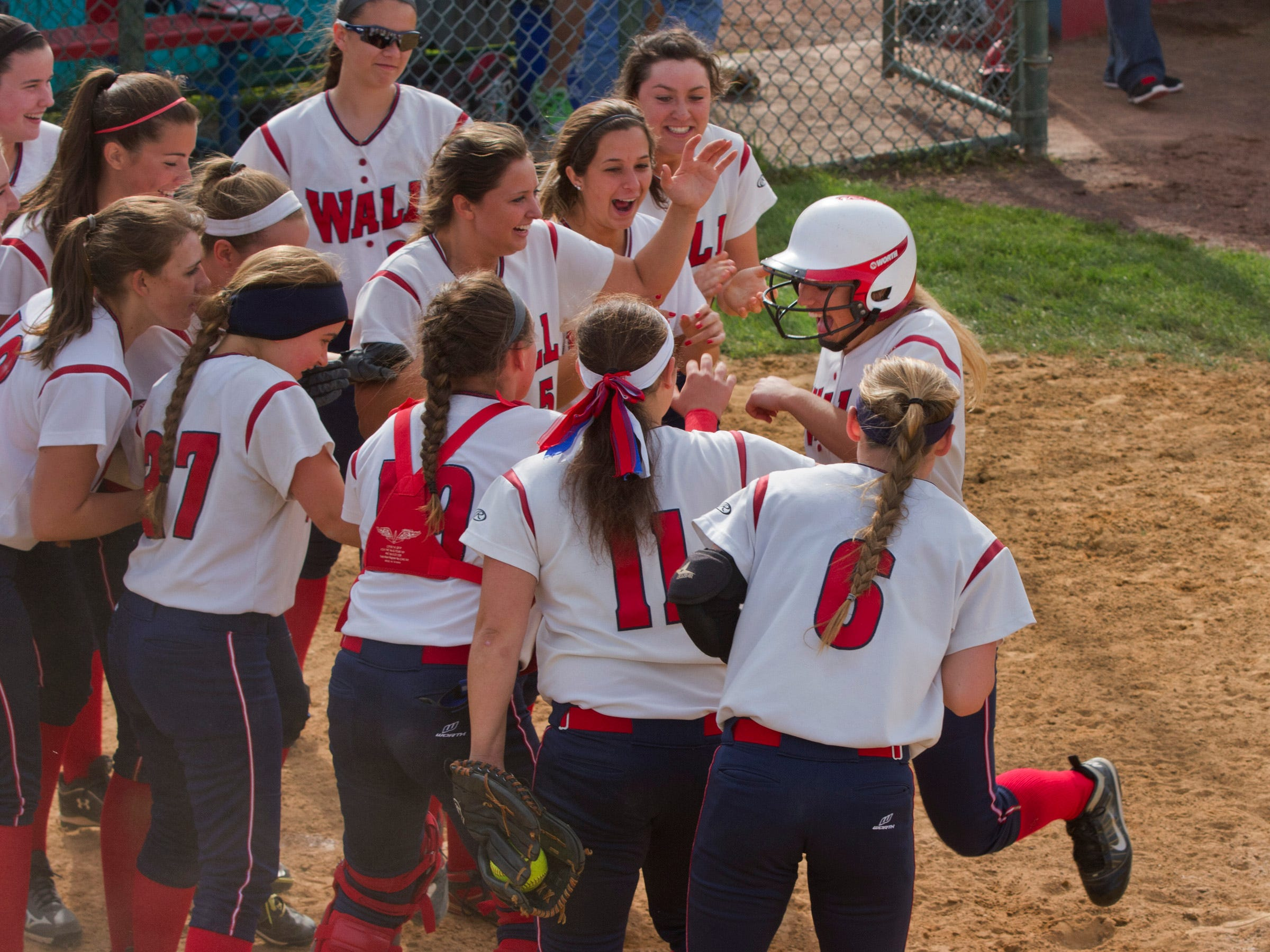 Wall players wait at home plate to pounce on Carly Layton after she hit a sixth-inning home run to put her team up 3-2 against Jackson Liberty in an NJSIAA Central Group III game in Wall on Wednesday.