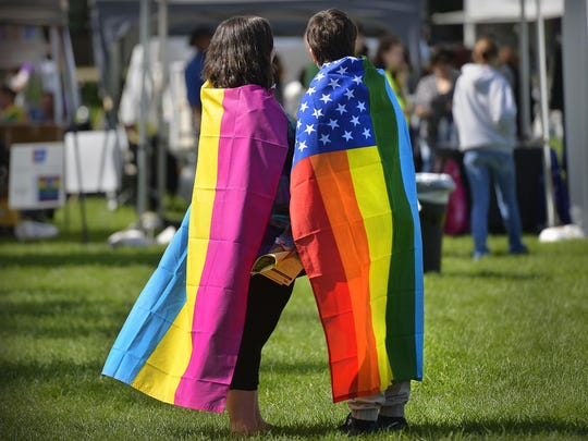 In this 2015 file photo from St. Cloud's Pride in the Park event at Lake George, a couple wear flags in support of the St. Cloud Pride.