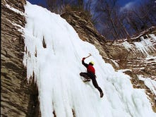 Former Cornell Outing Club secretary Brendan Kelly works his way up an ice covered cliff face. Kelly is belayed by Simeon Warner near Van Natta's Dam of Six Mile Creek in January 2004, during the Light in Winter Festival. The City of Ithaca issued a permit for the climb. A study is underway to determine if ice climbing could be done on a regular basis in Tompkins County.