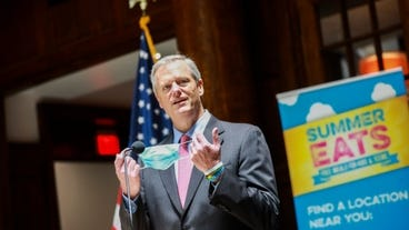 Gov. Charlie Baker holds his mask as he takes to the podium while visiting the YMCA of Greater Boston last week.