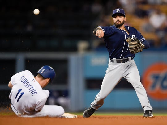 San Diego Padres second baseman Carlos Asuaje, right, throws to first after forcing out Los Angeles Dodgers' Logan Forsythe to complete the double play during the seventh inning of a baseball game in Los Angeles, Monday, Sept. 25, 2017. Austin Barnes was out at first. (AP Photo/Kelvin Kuo)