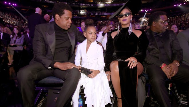 Beyoncé Knowles, in all black, sits at the Grammys with Jay-Z and Blue Ivy.