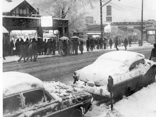 A crowd gathers around the scene of the shooting of