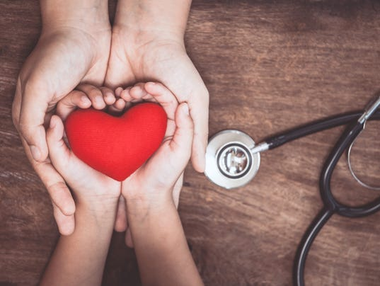 Red heart on woman and child hands and with doctor's stethoscope on wooden background
