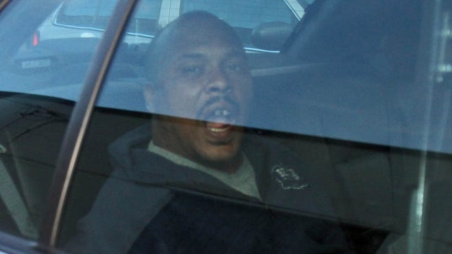 Howard J. Mickens, 31, of White Plains sits in a police car as he is driven from the Metropolitan Transportation Authority police department in Mount Vernon Sept. 25, 2013.