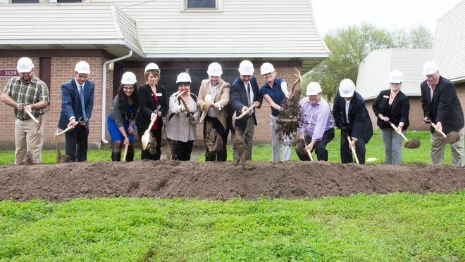 Corpus Christi city officials and project stakeholders scoop up dirt with shovels during the groundbreaking event for the Lexington Manor affordable housing complex March 4.