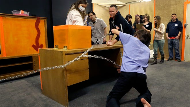 """In Detroit, a chained zombie reaches for participants as they play """"Trapped in a Room With a Zombie."""" Up to a dozen people are locked in a room for an hour alongside a zombie that's chained to a wall. Every five minutes, a buzzer sounds, and the zombie is given another foot of chain, allowing the undead creature to scamper even closer to its next meal. If participants don't solve a series of puzzles within the 60 minutes, the zombie """"eats"""" everyone in the group."""