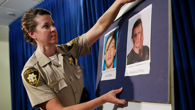 Las Vegas Metropolitan Police Department Officer Laura Meltzer hangs up pictures of suspects Jerad Miller and Amanda Miller before a news conference June 9, 2014 in Las Vegas.