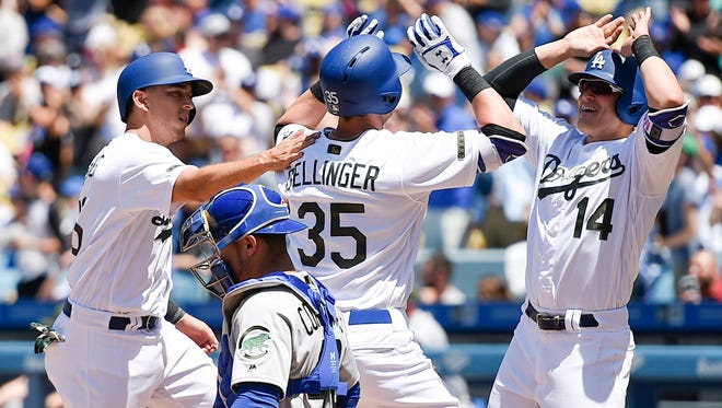 Cody Bellinger celebrates with Kiki Hernandez and Austin Barnes (left) after Hernandez hit a three-run home run against the Chicago Cubs.