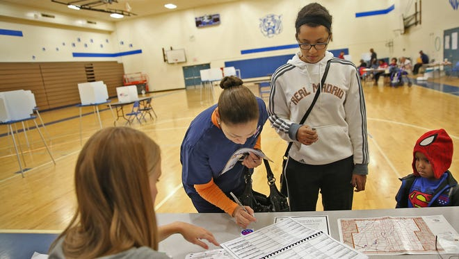 Xochitl Smith (from left) signs in to vote with her daughter Alexandria Thomas, who also voted, and Thomas' nephew Drew Jones, 3, on Election Day, Nov. 3, 2015, at the Westlane Middle School polling site in Indianapolis.