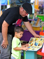 Steve Barosi and son Michael, 31/2, check out a book on big machines at one of the vendor booths.